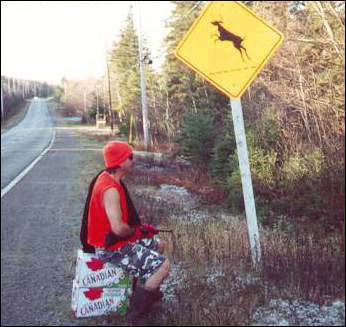 man waits for deer by deer sign